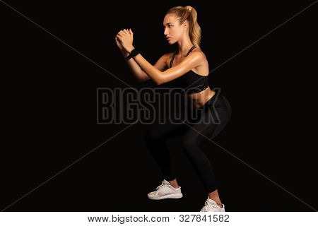 Fitness Girl Doing Deep Squat Exercise Posing Over Black Studio Background. Empty Space For Text