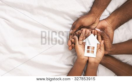 Adoption Concept. Black Family Of Three Holding Paper House Figure In Hands Over White Bed Sheet Bac