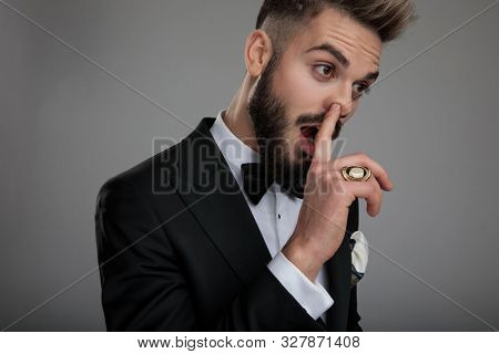 Close up of a clumsy groom picking his nose and showing his ring while wearing tuxedo and bowtie, standing on gray studio background