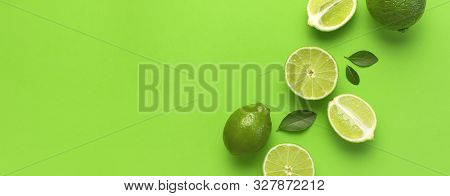 Fresh Juicy Lime And Green Leaves On Bright Green Background. Top View Flat Lay Copy Space. Creative