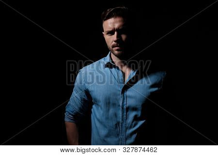 mysterious casual man wearing blue shirt standing in the shadows and staring at camera with hidden eyes against black studio background