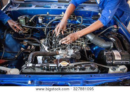 African Mechanics Repairing A Vintage Car Engine With Carburetor