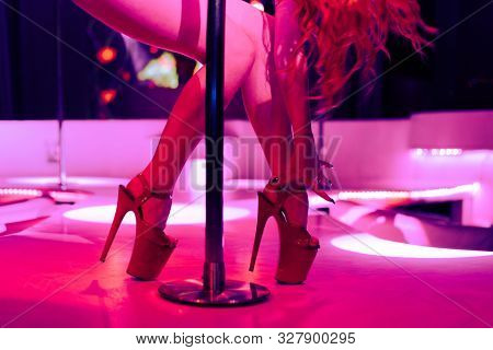 Heels Of Sexy Woman Pole Dancing Or Striptease. Pylon In Night Club. Stripper Girl Background