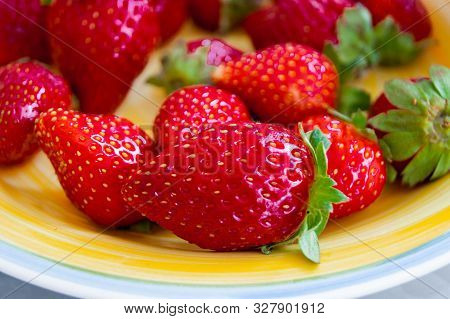 Red Berries Of Garden Strawberries With Green Sepals On A Sunny Yellow Porcelain Plate.