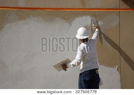 Stucco on a building wall. An unidentifiable contractor applies Stucco or Wall Texture to the outside of a building wall in preparation of painting the building. Wall and Building Repair and Patching