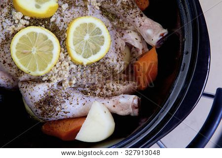 Chicken And Vegetables Cooking In A Slow Cooker With Herbs And Lemon.