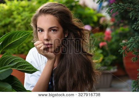 Charming Portrait Of A Pretty Teenage Girl Among Green Leaves. Healthy Hair, Clean Skin, In Harmony