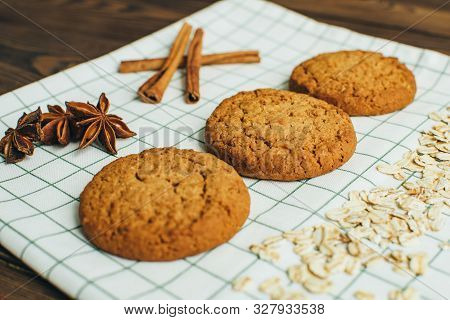 Three Tasty Oatmeal Cookies, Flakes, Sticks Of Cinnamon, Stars Of Badyan Laying At The Green Checker