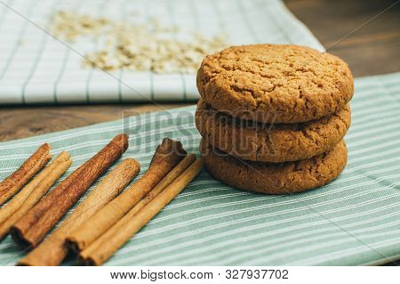 Close-up Three Tasty Oatmeal Cookies With Sticks Of Cinnamon Laying At The Green Stripped Textile Ki