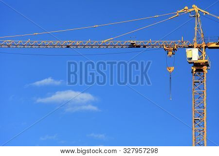 Single Construction Crane On The Blue Sky Background. Building Construction Site With Crane. The Con