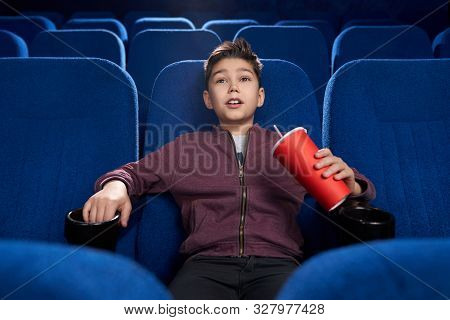 Selective Focus Of Strained Boy Watching Horror Movie In Cinema. Afraid Teen Drinking Aerated Sweet