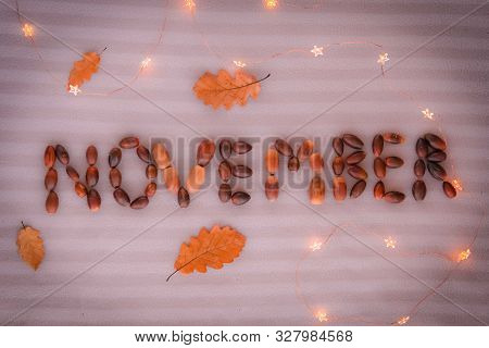 November Text. November Sign Made Of Acorns And Decorated With Yellow Oak Leaves And Lights On Grey