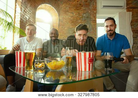 poster of Group of excited friends playing video games at home. Male gamers or fans spending time and having fun together at home. Emotional, expressive, exciting gameplay. Modern tech, friendship, weekend.
