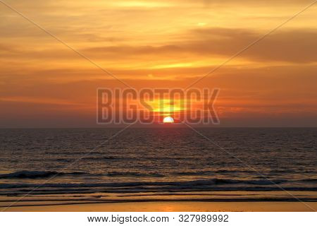 Beautiful Red Sunset Over The Ocean. Bright Sunset With Large Yellow Sun Under The Sea Surface. Sund