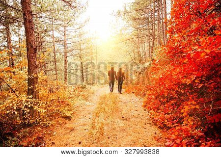 Couple Weared In Autumn-style Clothes Sweaters Family Look Running Through The Autumn Landscape. For