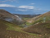 Landmannalaugar colorful Rhyolit mountains with steam from hot spring on famous Laugavegur trek. Fjallabak Nature Reserve in Highlands of Iceland, summer blue sky. poster