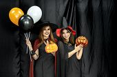 Two teenages and young adult girl women in Halloween costume for Halloween party background poster