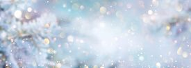 Christmas winter blurred background. Xmas tree with snow decorated with garland lights, holiday festive background. Widescreen backdrop. New year Winter art design, wide screen holiday border