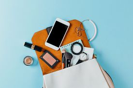 Fashion Concept : Flat Lay Of Brown Leather Woman Bag Open Out With Cosmetics, Accessories And Smart
