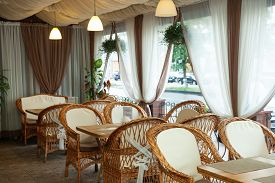 Wicker Chairs And Tables On The Terrace In The Interior Of The Cafe