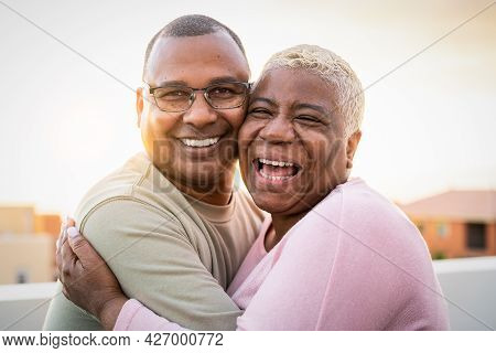 Happy Latin Senior Couple Having Romantic Moment Embracing On Rooftop During Sunset Time - Elderly P
