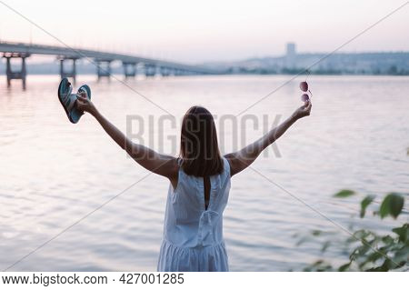 Rear View Of A Young Woman With Her Arms Outstretched And Enjoying The Warm Summer Wind At Sunset On