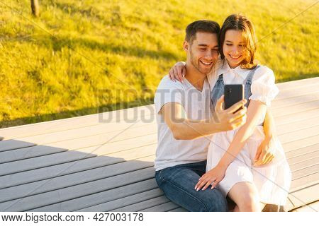 Happy Young Couple Hugging And Sharing Media In Smartphone Sitting Relaxed On Bench In City Park On