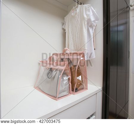 Open White Closet With Clothes And Bags And Empty Space