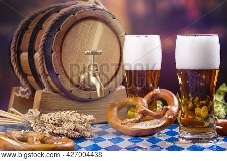 Oktoberfest Beer Barrel And Beer Glass, Pretzels, Wheat And Hops On Wooden Table
