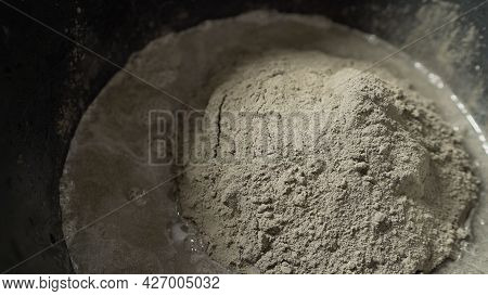 Preparation Of Cement Mix For Use In Tile Laying. A Close-up Of A Solution In A Bucket.