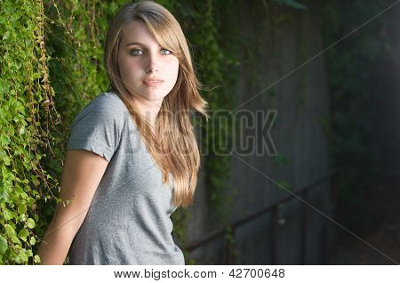 Teenage girl stands near vines in the shade facing right