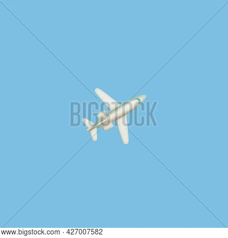 The Plane On A Blue Background. Concept Of Air Travel Or Travel. A Look From Above. A Small Toy Line