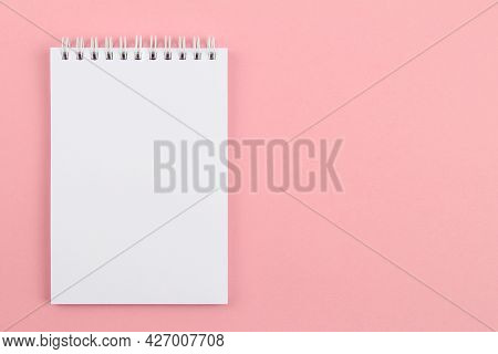 On A Pink Background-a Sketchbook Or An Unlined Notebook, Stitched With A Spring.an Empty Layout Is
