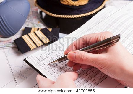 Close up of an airplane pilot hand filling in logbook with equipment including hat, epaulettes and other documents in background