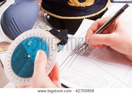 Close up of an airplane pilot hand with holding pattern calculator filling in an flight plan and with equipment including hat, epaulettes and other documents in background