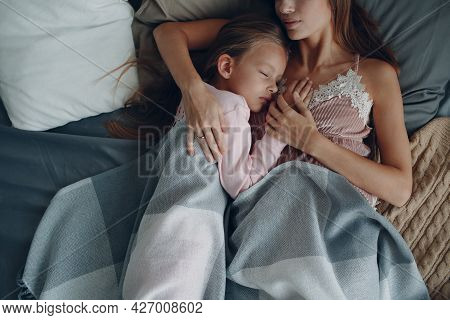 Mother And Little Daughter Child Girl At Sleep At Bed Home. Single Parenting And Motherhood.