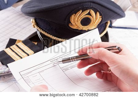 Close up of an airplane pilot hand filling in an flight plan and pre-flight checklist with equipment including hat, epaulettes and other documents in background