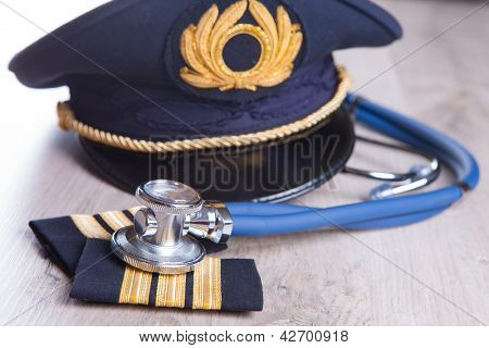 Close up of an airplane pilot equipment hat and epaluetes with doctor's stethoscope. Conceptual image of medical exam.