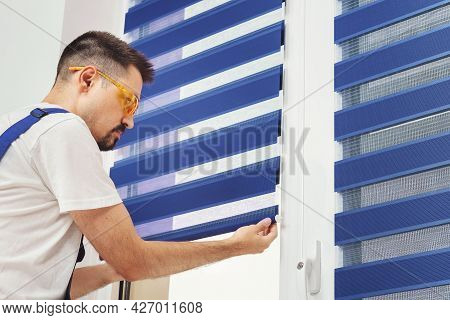 Male Builder Carpenter Pulling Down A Blue Jalousie On A Window. Repairing And Inspection Fabric Cur