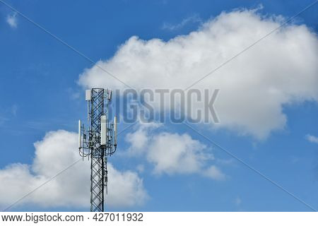 Telecommunication Towers With Motions Clouds On Blue Sky Background.
