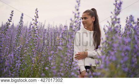 Smiling Beautiful Brunette In The Lavender Field. Beautiful Girl In Flowers On A Meadow.