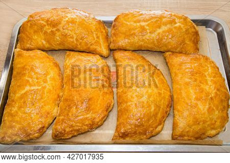 Baked Puff Pastry With Delicious Yellow Cheese On A Metal Tray. Bakery Products National Traditional