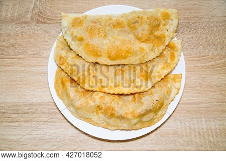 Chebureks With Meat Or Pie Of Yellow Appetizing Color On A White Round Plate On A Wooden Board Backg