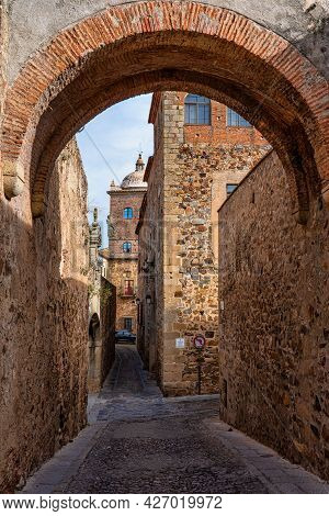 Narrow Alley With Old Stone Buildings At Caceres, Extremadura, Spain. A Cute And Charming Town With