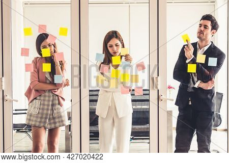 Unhappy Business People Feel Disappointed While Looking At Sticky Note On The Windows In The Office.