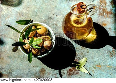 Bottle Of Of Olive Oil With Fresh Olives And Olive Branch On Vinttage Green Table. Top View Of Olive