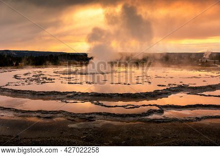 Fountain Geyser Basin With Steam Smoke In Firehole Lake Reflect The Golden Sunset Sky To Water Surfa