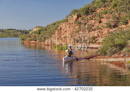 canoe paddler (senior male) on a mountain lake - Horsetooth Reservoir near Fort Collins, Colorado at springtime