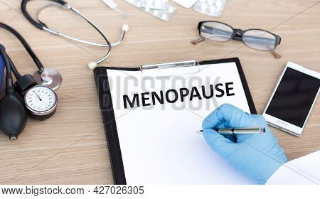 Doctor's Hand Writes A Diagnosis, Text Menopause With Hand Holding A Pen. Medical Concept.