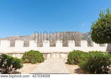 Castle Ramparts With Path Leading To Barrier Between Trees In Guadalest, Spain Ancient Town With Med